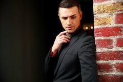 Pensive businessman standing near brick wall Stock Photos