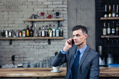 Pensive businessman talking on the phone in cafe Royalty Free Stock Photos