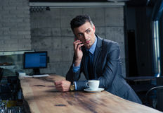 Pensive businessman talking on the phone in cafe Stock Images