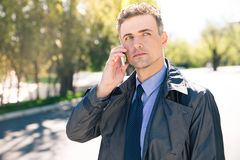 Pensive businessman talking on the phone outdoors Stock Photography