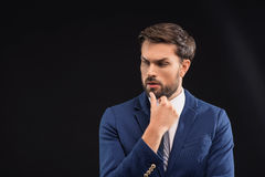 Pensive businessman thinking about something seriously. Clever young man is making serious decision. He is standing in suit and touching chin pensively.  and Stock Photo