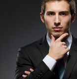 Pensive businessman touches his face Stock Image