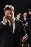Pensive businessman using smartphone while business people connecting behind Stock Images