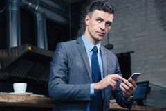 Pensive businessman using smartphone in cafe Royalty Free Stock Image