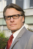 Pensive businessman wearing spectacles. A handsome forties businessman wearing spectacles and looking intelligent is looking away from camera as he stands in Royalty Free Stock Photo