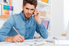 Pensive businessman working with documents while talking on the phone Royalty Free Stock Photos