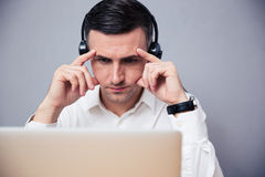 Pensive businessman working on laptop with headphones Stock Photo