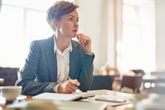 Pensive Businesswoman at Coffeehouse Royalty Free Stock Images