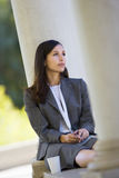 Pensive businesswoman, in grey suit, sitting alone on coffee break, daydreaming (tilt) Stock Images