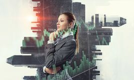 Businesswoman making desicion. Pensive businesswoman with hand on chin modern buildings and infographs Royalty Free Stock Image