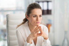 Pensive businesswoman with hands in steeple position Royalty Free Stock Photo