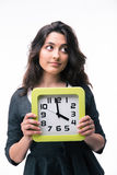 Pensive businesswoman holding clock Stock Images