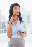 Pensive businesswoman holding a tablet pc Royalty Free Stock Photography