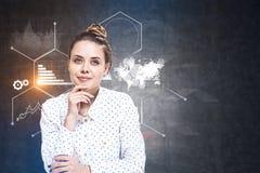 Pensive businesswoman, infographics on blackboard stock images