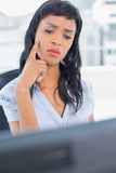 Pensive businesswoman looking at her computer Stock Image