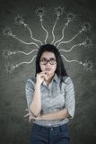 Pensive businesswoman with many arrows and bulbs Royalty Free Stock Images