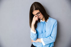 Pensive businesswoman over gray background Stock Photos