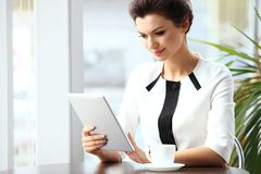 Pensive businesswoman reading an article on tablet computer Royalty Free Stock Photo