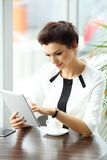 Pensive businesswoman reading an article on tablet computer Stock Images