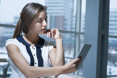 Pensive businesswoman reading from digital tablet Royalty Free Stock Photo