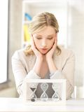 Pensive businesswoman with sand glass Stock Photo