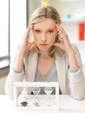 Pensive businesswoman with sand glass royalty free stock photos