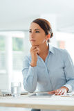 Pensive businesswoman sitting at  desk Stock Photos