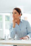 Pensive businesswoman sitting at  desk Stock Photos