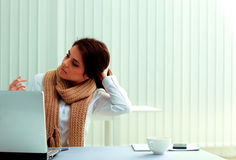 Pensive businesswoman sitting on her workplace and looking away Stock Image