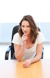 Pensive businesswoman sitting at a table Royalty Free Stock Image