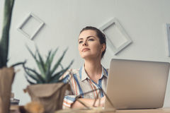 Pensive businesswoman sitting at table with laptop in modern office. Attractive pensive businesswoman sitting at table with laptop in modern office Stock Photography