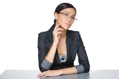 Pensive businesswoman sitting at the table Royalty Free Stock Image