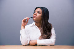 Pensive businesswoman sitting at the table with pen Stock Image