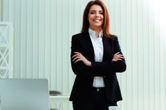 Pensive businesswoman standing with arms folded Stock Photography