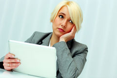 Pensive businesswoman with tablet computer looking away Stock Images
