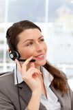 Pensive businesswoman talking on the phones. Using headphones in her office Royalty Free Stock Photo