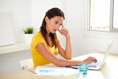 Pensive businesswoman thinking at her office. Pensive businesswoman thinking while using the web at her office Royalty Free Stock Photo
