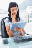 Pensive businesswoman using a tablet pc Stock Photography