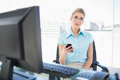 Pensive businesswoman wearing glasses text messaging Royalty Free Stock Photo
