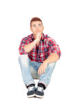 Pensive casual boy sitting on the floor Stock Images