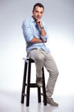Pensive casual man on a chair Royalty Free Stock Images
