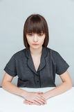 Pensive casual woman sitting at the table Stock Images