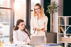 Pensive caucasian businesswomen in formalwear talking while working at modern office. Young pensive caucasian businesswomen in formalwear talking while working Royalty Free Stock Images