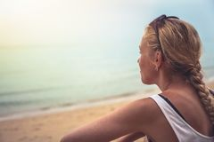 Pensive cheerful woman tourist relaxing on beach looking into horizon during sunset at tropical beach. Pensive cheerful woman tourist relaxing on tropical beach Royalty Free Stock Photos