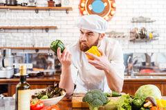Pensive chef cook choosing vegetables for salad on the kitchen Stock Image
