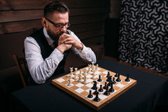 Pensive chess player thinking about game strategy. Pensive male chess player in glasses thinking about game strategy. Intelligence competition concept royalty free stock photography