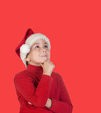 Pensive child with blond hair and Christmas hat Stock Photos