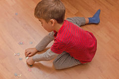 Pensive child collects puzzles Stock Photo