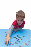 Pensive child collects puzzles Stock Photos