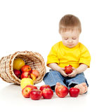 Pensive child eating healthy food. Pensive child with basket filling red apples Royalty Free Stock Images